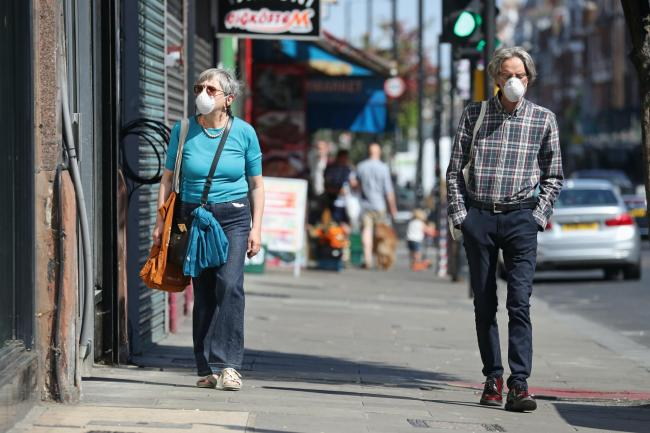 People wearing face masks walk past closed shops