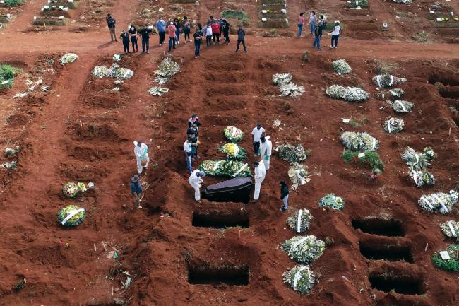 Cemetery workers wearing protective gear lower the coffin of a person who died from complications related to Covid-19 into a gravesite in Brazil