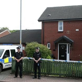 Police outside a house in the Hulme area of Manchester after the bodies of two women were found